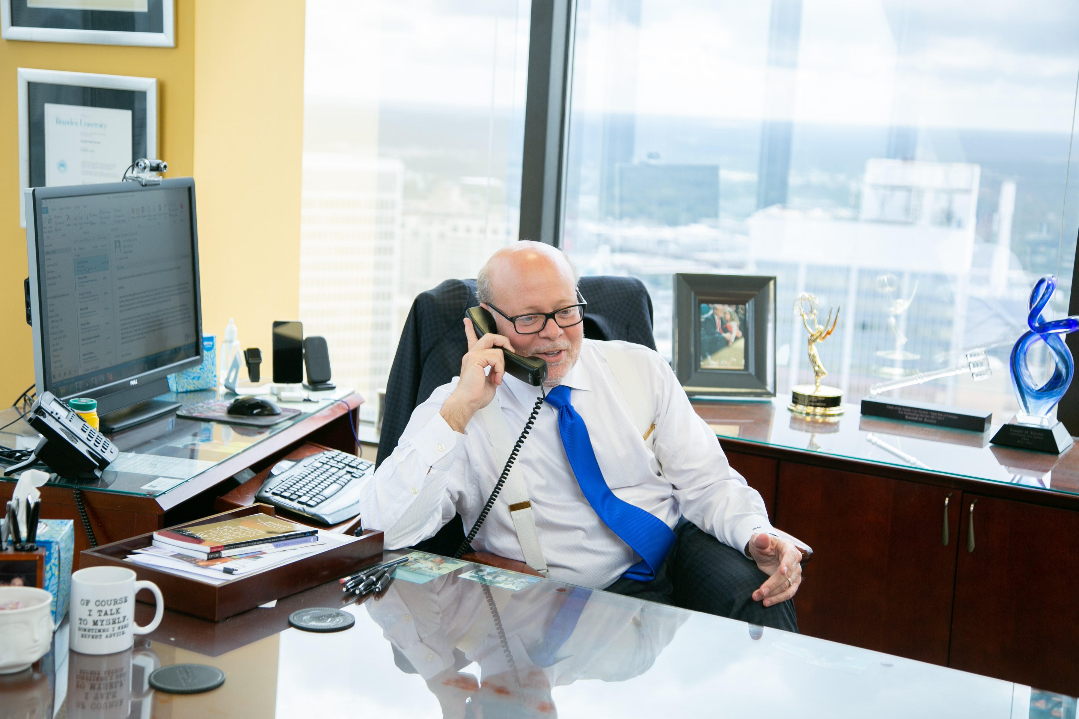 divorce lawyer randall kessler taking a phone call in his office with an emmy in the background